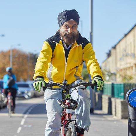 Man in turban cycling on segregated route