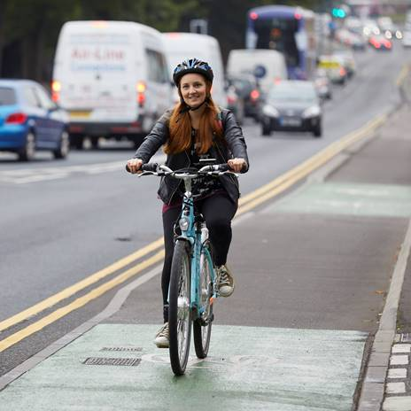 Woman in helmet cycling on segreagated cycle lane