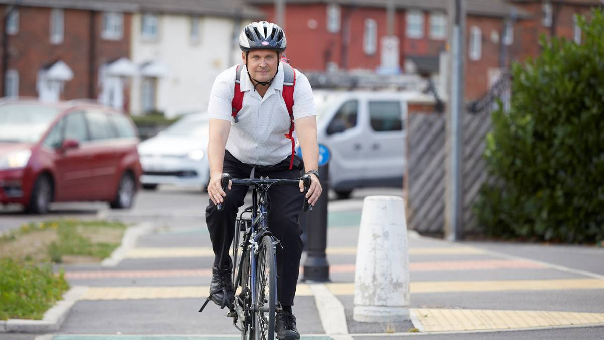 Man with rucksack on bike on cycle route