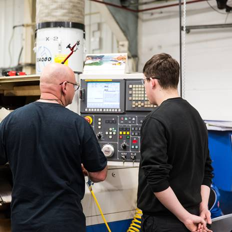 Man teaching a student on machinery