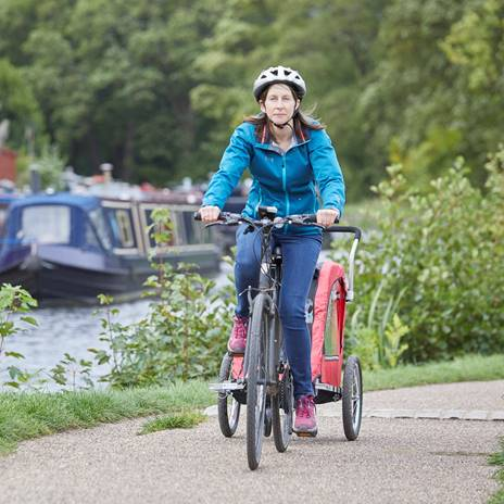 Woman cycling on canal towpath with trailer