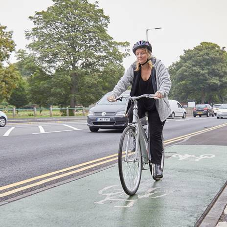 Woman riding bike along cycle lane