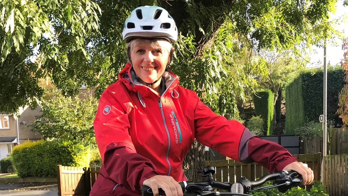 Woman wearing helmet on a bike in front of a tree