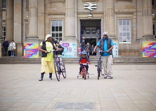Woman, child and man with bikes outside Huddersfield Train Station