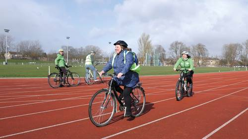 Woman cycling on athletics track at Thornes Park Stadium, Wakefield