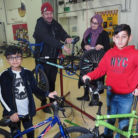 2 children and 2 adults with bikes in school hall