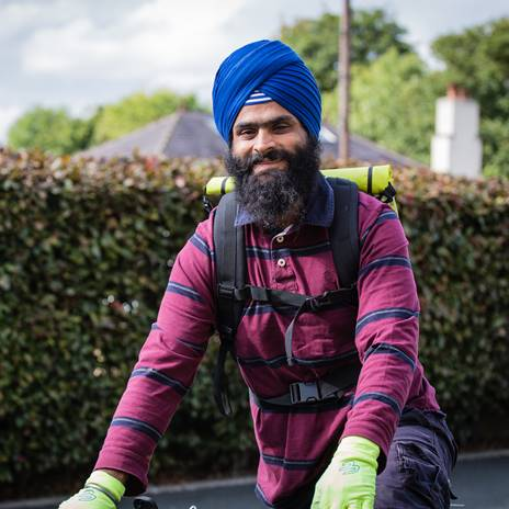 Man in turban on a bike in front of a hedge